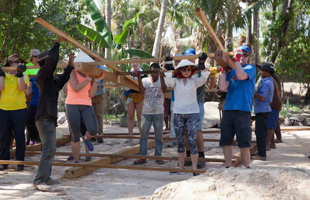 Volunteers lift the house frame of a VBC house
